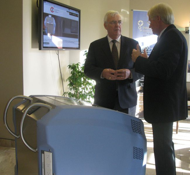 John Gerretsen, left, MPP for Kingston and the Islands, and Dr. Michael Shannon, stand in front of the AsepticSure system, developed by Dr. Shannon and Dr. Dick Zoutman at the Innovation Park facility. (Hilary Thomson/For The Whig-Standard)