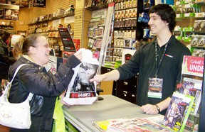 Terri Gibeault accepts her purchase from Phillip Melo, assistant manager of Game Stop in the Cornwall Square, after buying a Christmas gift for her son last year. File photo