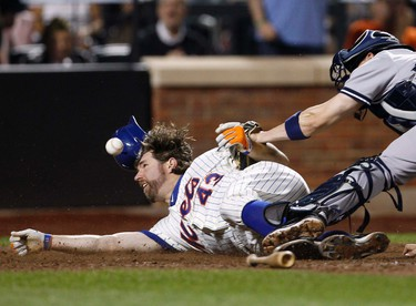 New York Mets' R.A. Dickey (L) scores as the ball gets away from New York Yankees catcher Chris Stewart during the fifth inning of their MLB Interleague baseball game at Citifield in New York, June 24, 2012. REUTERS/Adam Hunger