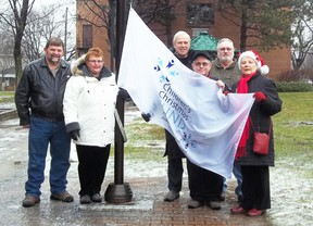 City hall raised a flag in support of the Children's Christmas Fund. Joining the celebration were Children's Christmas Fund representatives Terry Muir, Theresa Taylor, Peter Morgan, Marvin Plumadare and Lee Cassidy, along with Mayor Bob Kilger (centre). Staff photo/KATHRYN BURNHAM