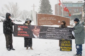 """Pro-life activists picket outside the Sudbury Catholic District School Board with a banner featuring Justin Trudeau's face and a quote saying: """"As a politician I have political positions on gay marriage and abortion that don't at all resemble those of the Catholic Church."""""""