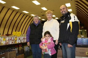 Deb Flewelling, left, and Shirley Simons of the Paris Community Christmas Hamper program got a helping hand on Wednesday, Dec. 19, 2012 from Rob Santos and his daughter Kali, 4, to ready the hampers for 140 families in need of some help to have a nice Christmas. MICHAEL PEELING/THE PARIS STAR/QMI AGENY