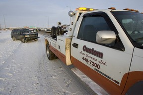A tow truck driver with Custom Auto Carriers Ltd. and an Edmonton Police Service officer responded to a two vehicle collision in the southbound lane of Highway 2 in Edmonton, Alta., on Sunday, December 23, 2012. Police say a high number of crashes have occured due to inclement weather. Ian Kucerak/Edmonton Sun/QMI Agency