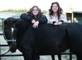 Identical twins Kourteney (right) and Kaitlynn Lappan, who are autistic, pose withKourteney's horse River. The two girls discovered their talent for showing horses this summer.