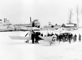 77.830.58.09  Wop May and Vic Horner in Peace River, Jan. 3, 1929, n their return to Edmonton following their Mercy Flight to Fort Vermilion. Note: the plane has wheels not skis. In the background of the photograph (l-r) S. S. D.A. Thomas, S. S. Athabasca River, which by at least one account was abandoned, and S. S. Weenusk.