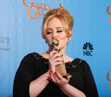 """Adele, winner for Best Original Song - Motion Picture, for """"Skyfall"""" from the film of the same name, poses with her award backstage at the 70th annual Golden Globe Awards in Beverly Hills, California, January 13, 2013.  REUTERS/Lucy Nicholson (UNITED STATES  - Tags: ENTERTAINMENT)  (GOLDENGLOBES-BACKSTAGE)"""