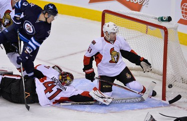 Ottawa Senators' Andre Benoit (R) helps goaltender Craig Anderson as the Winnipeg Jets take a shot on net during the second period of their NHL hockey game in Winnipeg January 19, 2013. REUTERS/Fred Greenslade  (CANADA - Tags: SPORT ICE HOCKEY)
