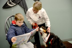 Six year old Eamon Crook of Trenton reads to Grace, a nine-year-old Bernese Mountain Dog at the Quinte West Public Library Trenton branch Thursday afternoon, during the kickoff of the library's Paws for Reading – a therapeutic reading program that uses dogs to help children overcome fears and anxiety of reading aloud. Also shown is Grace's owner and St. John Ambulance volunteer Gail Conrick.  EMILY MOUNTNEY/TRENTONIAN/QMI AGENCY
