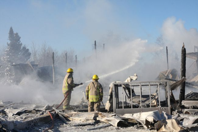 Volunteer firefighters extinguish hot spots at a Dowling barn fire on Thursday. JOHN LAPPA/THE SUDBURY STAR/QMI AGENCY