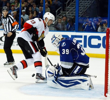Tampa Bay Lightning's goalie Anders Lindback (R) makes a save on a breakaway by Ottawa Senators' Peter Regin during the first period of their NHL hockey game in Tampa, Florida January 25, 2013.  REUTERS/Mike Carlson (UNITED STATES)