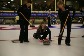 Thornhill Bayview skip Julie Hastings releases a shot while lead Katrina Collins, left, and second Stacey Smith prepare to sweep during her eighth-round game against Marlo Dahl of Thunder Bay Port Arthur at the Ontario Scotties Tournament of Hearts Friday at the K-W Granite Club. Hastings won 8-3 to secure at least a tiebreaker spot with one round-robin draw left. (STEVE GREEN/The London Free Press)