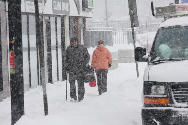People walk down a snow-covered street in Sudbury on Jan. 28, 2013. With 15 cm of snow expected, cops are warning to be extra cautious on area streets, sidewalks and highways.