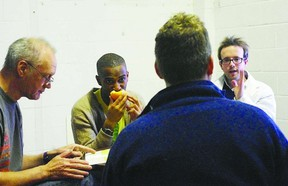 Director Alan Dilworth, (back to camera), speaks with (l-r) Nigel Bennett, Ayinde Blake and William Matthews as they rehearse a scene from Blue/Orange playing at the Baby Grand Theatre until Feb. 16.