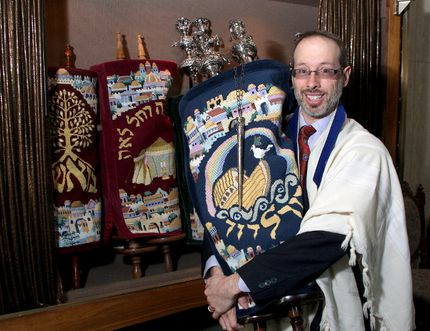 Rabbi L. Shalom Plotkin at the Beth Israel Synagogue on Tuesday with one of the synagogue's Torahs. (Ian MacAlpine The Whig-Standard)