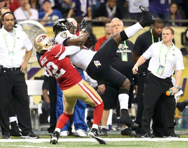 Baltimore Ravens wide receiver Anquan Boldin (81) hangs on to a pass as he tackled by San Francisco 49ers cornerback Carlos Rogers (22) during the fourth quarter in the NFL Super Bowl XLVII football game in New Orleans, Louisiana, February 3, 2013. (REUTERS/Sean Gardner)