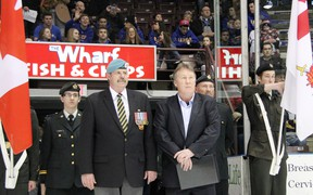 Jerry Brooks, front left, stands with Bill Abercrombie, Sarnia Sting VP of hockey operations, at a Jan. 17, 2013 game at the RBC Centre in Sarnia, Ont. The retired Canadian Forces sergeant is one of several military personnel honoured as part of the Sting's Veteran's Way program this season. PAUL OWEN/THE OBSERVER/QMI AGENCY