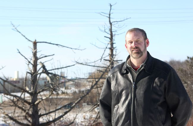 Jeff Scott, the councillor representing the Countryside District, stands at an island bordered by Hwy. 401 and Division Street in Kingston. Behind him are a number of dead trees, originally planted by the Ministry of Transportation during highway projects. Scott is calling on the ministry to change its policy to include maintaining and removing dead trees from the edges of its highways. 
