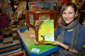 Elly MacKay with her first children's book If You Hold A Seed, which she authored and illustrated, at a launch at The Rocking Horse in downtown Owen Sound on Saturday. MacKay did a reading of the book and signed copies for those who purchased them.