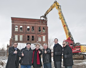 (From left) Mayor Chris Friel, city councillors Dave Neumann, Marguerite Ceschi-Smith, John Utley, manager of policy and planning Paul Moore, and ProGreen Demolition general manager Joe Batista give the thumbs up on Monday as demolition gets underway at the 66 Mohawk Street brownfield site. (BRIAN THOMPSON The Expositor)