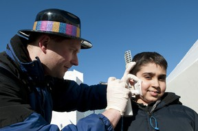 Greg Woudstra, an artist with TempTattoos, gives Rohan Sharma, 9, a spray-painted snowflake tattoo during the Metropolis Edmonton International Winter Festival at Churchill Square, in Edmonton, Alberta, on Feb. 20, 2012. The festival wrapped up on Family Day with both outdoor and indoor activities for the thousands of visitors to the downtown square next to Edmonton's city hall. IAN KUCERAK/QMI AGENCY