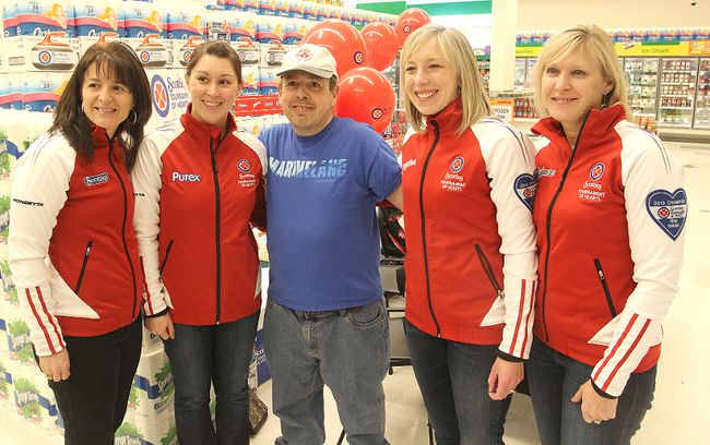 Special Olympics curler Ian Bruce, centre, has his picture taken with Team Canada curlers Heather Nedohin, left, Jessica Mair, Beth Iskiw and Laine Peters as they greeted wellwishers and signed autographs to promote the Scotties Tournament of Hearts at a Kingston grocery store Thursday morning.