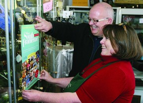 Wayne Orr, chief administrative officer for the Township of South Frontenac, and Christine Kennedy, owner of Memory Lane Flowers and Gifts in Sydenham, hang a poster announcing the Shop South Frontenac campaign, encouraging residents to shop local in South Frontenac.       Rob Mooy - Kingston This Week / Frontenac This Week