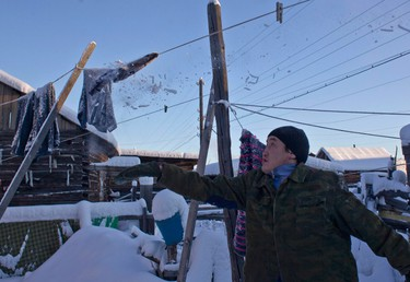 Igor Vinokurov, 35, knocks snow and ice off a frozen washing line in the village of Oymyakon, in the Republic of Sakha, northeast Russia, January 26, 2013. The coldest temperatures in the northern hemisphere have been recorded in the Oymyakon valley, where according to the United Kingdom Met Office a temperature of -67.8 degrees Celsius (-90 degrees Fahrenheit) was registered in 1933 - the coldest on record in the northern hemisphere since the beginning of the 20th century. Yet despite the harsh climate, people live in the valley, and the area is equipped with schools, a post office, a bank, and even an airport runway (albeit open only in the summer).    Picture taken January 26, 2013.    REUTERS/Maxim Shemetov