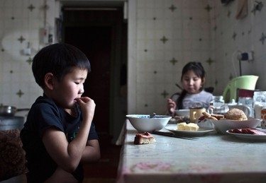 Nikolay Vinokurov, 7, and his sister Vera Vinokurova, 9, have lunch at their grandmother's house in the village of Tomtor, in the Republic of Sakha, northeast Russia, January 21, 2013. The coldest temperatures in the northern hemisphere have been recorded in Sakha, the location of the Oymyakon valley, where according to the United Kingdom Met Office a temperature of -67.8 degrees Celsius (-90 degrees Fahrenheit) was registered in 1933 - the coldest on record in the northern hemisphere since the beginning of the 20th century. Yet despite the harsh climate, people live in the valley, and the area is equipped with schools, a post office, a bank, and even an airport runway (albeit open only in the summer). Picture taken January 21, 2013. REUTERS/Maxim Shemetov