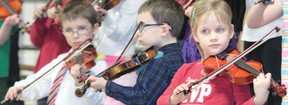 Cayley School Grade 1 students show their perfect postures for playing violins during the school's Valentine's Day tea Feb. 14, 2013.