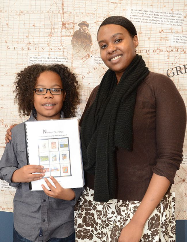 "Raeon George-Robinson and his mother Rhonda George at Grey Roots Saturday to launch Vol. 10 of ""Northern Terminus: The African Canadian History Journal"". The two wrote an essay together for Volume 10 about a school field trip to Priceville to learn more about the area's black history. Raeon, 10, became inspired to learn more about black history because of U.S. President Barack Obama."