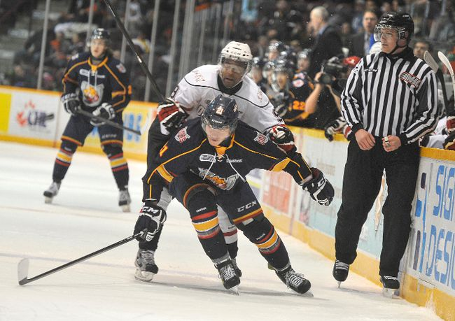 Brendan Lemieux of the Barrie Colts ducks under Gemel Smith of the Owen Sound Attack during first period action Thursday at the Barrie Molson Centre.