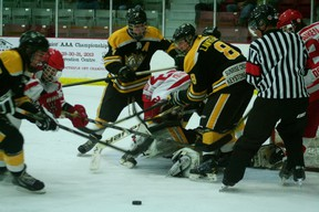 Kenora Midget Thistles' Mikko Keski-Pukkila gets thrown to the ice by two Brandon Wheat Kings after trying to find the rebound in front of the net. The Thistles lost the game 4-3 and subsequently lost the series 3-0.   GRACE PROTOPAPAS/KENORA DAILY MINER AND NEWS