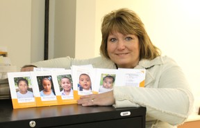 Susan Hodges shows pictures of some of the children she will get to meet when she travels to Nicaragua next month.