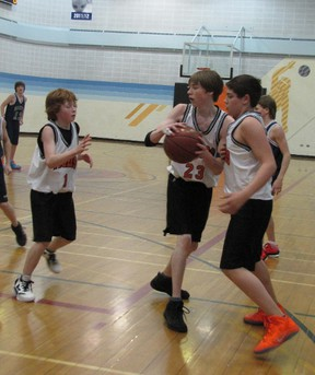 Mayerthorpe Junior Senior High School junior Tigers, from left,  Terin Roberts, Jesse Lasher, and Keith Stensrud, cluster around the ball in a game against the St. Joseph High School.