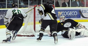 Trenton Golden Hawks' Victor Adamo reaches back in vain for Cody Mintz's knuckle puck that completes a four-game sweep for the Cobourg Cougars Monday night at the Cobourg Community Centre.