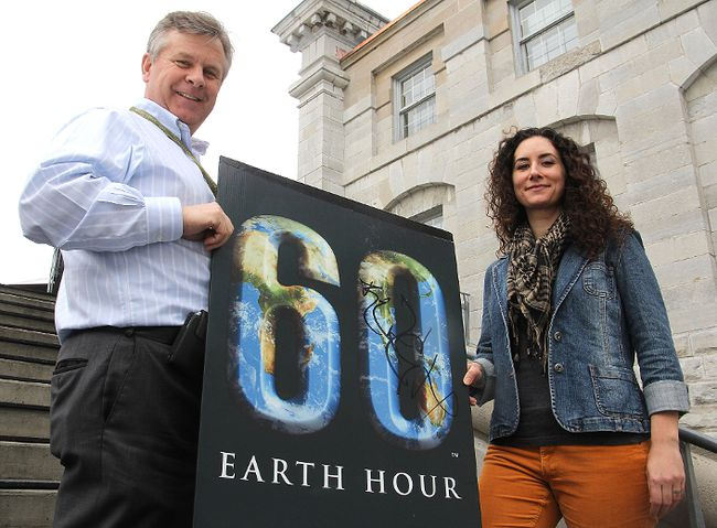 Joe Davis, from Sustainable Kingston, and Tricia Knowles, a co-founder of Unplugged Kingston and the Earth Hour observance, hold a poster promoting this year's Earth Hour, which will be held Sat., March 23 at 8:30 p.m.