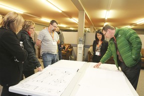 Members of public and Genivar staff examine the designs for the second phase of the Main Street Revitalization project at a recent open house March 4.