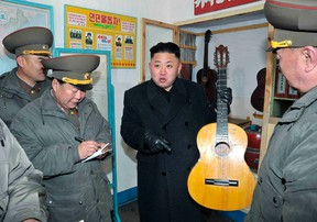 North Korean leader Kim Jong-Un (C) holds a guitar during his visit to a military unit on the Wolnae Islet Defence Detachment in the western sector of the front line, which is near Baengnyeong Island of South Korea March 11, 2013 in this picture released by the North's official KCNA news agency in Pyongyang March 12, 2013. (REUTERS/KCNA)