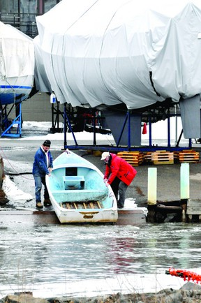 John Panter, left, and John Donaghue pull a boat a little further up the ramp at the Brockville Yacht Club as Buell's Creek continued to rise this week. (DARCY CHEEK/The Recorder and Times)