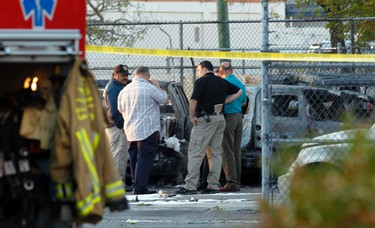 Police and fire investigators stand next to burned cars where a small twin-engine plane crashed into parked vehicles and burned shortly after takeoff from Fort Lauderdale Executive Airport in Fort Lauderdale, Florida March 15, 2013. (REUTERS/Bob Sullivan)