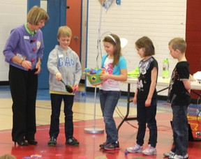 Carol McCloud directs Clandonald Grade 2 students in a skit to help the younger kids understand the bucket method.