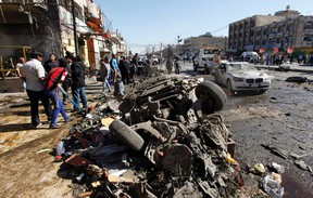 Residents gather at the site of a car bomb attack in the AL-Mashtal district in Baghdad on March 19, 2013. (REUTERS/Mohammed Ameen)