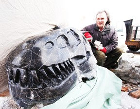 Mitch Wilson with his carved stone Albertosaurus skull, on his farm near Enterprise.