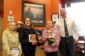Emily Cox, left, Emma Lawlor and Madison DiSalvo of Beverly Central School present Tim Hortons of Paris owner Rick Bowler with 10,159 pennies (about 60 pounds) they collected in February to donate to the Tim Horton Children's Foundation. The money will help underprivileged kids attend the Onondaga Farms camp near St. George. MICHAEL PEELING/The Paris Star/QMI Agency