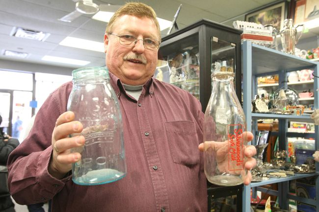 Ken Brown holds some old glass milk containers in his Main Street shop Friday morning. Brown is hoping his business, Brown's Vacuums, Antiques & Collectibles on Main Street, is one of several places featured in the hit reality show Canadian Pickers.