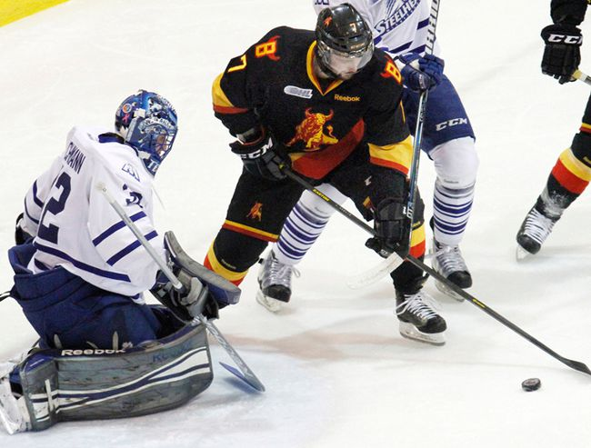 Belleville Bulls forward Michael Curtis is stopped by Mississauga Steelheads goalie and former Bull, Tyson Teichmann, during OHL playoff action Saturday night at Yardmen Arena. (Jerome Lessard/The Intelligencer)
