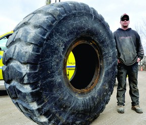 Chris Borden of Vanzuylen Alignment and Tire Service stands Wednesday beside a loader tire, one of the sizes included in a new tire eco-fee. (DARCY CHEEK/The Recorder and Times)
