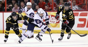 Kingston's Jayna Hefford, left, and Canadian teammate Marie-Philip Poulin try to check Julie Chu of Team USA during action a preliminary-round game at the Women's World Hockey Championship at Scotiabank Place in Ottawa on Tuesday night. (Errol McGihon/QMI Agency)