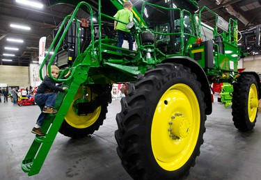 Reece Spicer, 2, climbs up to check out a sprayer behind brother Owen Spicer, 5, during Northlands Farm and Ranch Show at the Edmonton Expo Centre in Edmonton, Alta. on Friday, Apr. 5, 2013. Amber Bracken/Edmonton Sun/QMI Agency