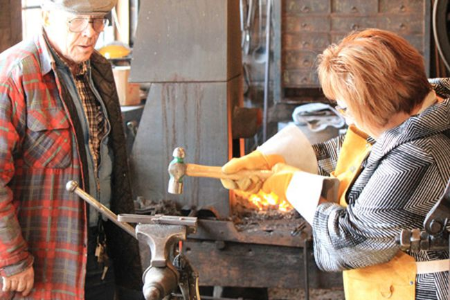 "Alberta Culture Minister Heather Klimchuk recieves a lesson in blacksmithing during the Lacombe stop on her ""Culture Connects"" tour."